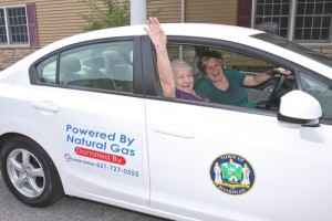 BARBARAELLEN KOCH PHOTO | Riverhead senior center aide Daryl Sulzer lets Etta Pietocha, 90, in the town's new natural gas vehicle after they just filled it up at National Grid property last year.