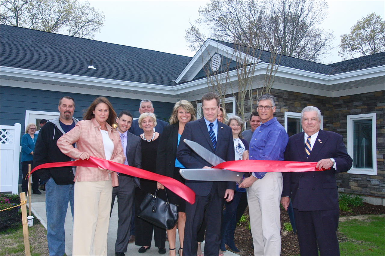 "Brian Stark, president of Stark Homes, which operates Glenwood Village, cuts the ribbon with town officials outside the newly renovated and expanded ""Clubhouse"" Wednesday afternoon. (Credit: Barbaraellen Koch)"