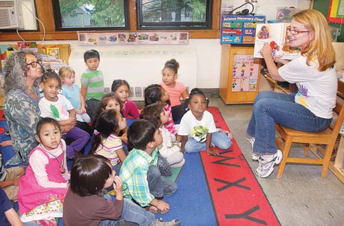 BARBARAELLEN KOCH PHOTO | Pre-k teacher Claudia Cipolla of Wading River reads a story to her students Friday in Riverhead about getting ready for kindergarten. Sitting with the children is Carol Burnett, the Head Start of Long Island's community outreach recruitment coordinator.