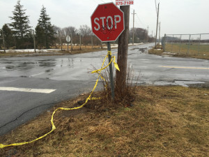 Police tape hangs from a stop sign the morning after the crash. (Credit: Cyndi Murray)