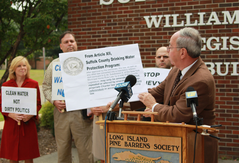"Pine Barrens Society head Richard Amper reads from the Suffolk County Drinking Water Protection Program in 2011, which states the law ""may only be amended, modified, repealed or altered by an enactment of an appropriate Charter Law subject to mandatory referendum."" (Credit: Jennifer Gustavson file)"