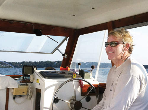 Former baykeeper Kevin McAllister at the wheel on the water. (Credit: Courtesy photo)