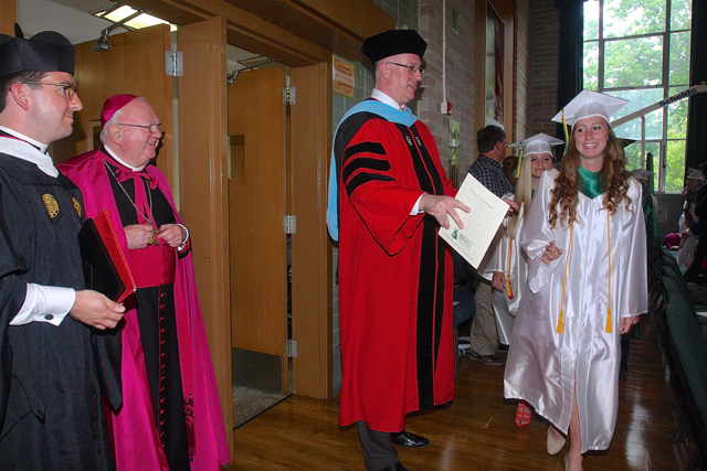 McGann-Mercy campus minister Matt Prochilo (left), Bishop William Murphy (center) and Principal Carl Semmler stood by as the graduates proceeded through the auditorium before the commencement ceremony Wednesday afternoon. (Credit: Barbaraellen Koch)