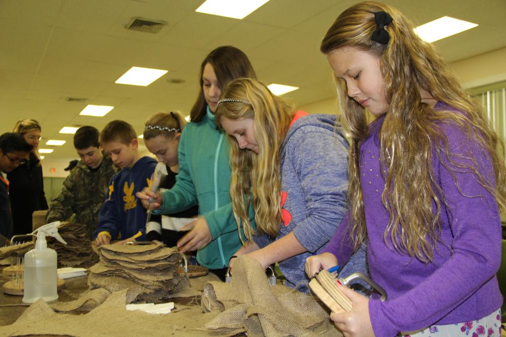 Sixth graders Lauren Onufrak,11, Emma Olsen, 11, and Myah Orlowski, 12, prepare burlap disks for Cornell researchers.