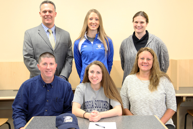 Joscelin Morrow was joined for a signing ceremony by her parents John (left) and Nancy (right). High School principal Charles Regan,  varsity coach Amy Greene and guidance counselor Suzzane Maurino joined her as well. (Credit: Riverhead Schools)