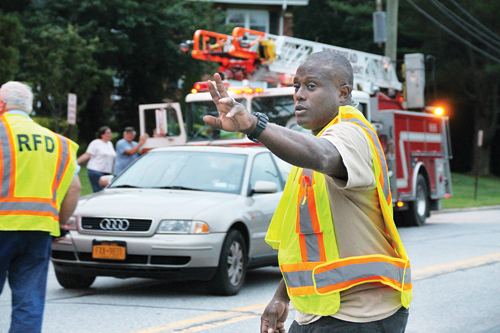 PAUL SQUIRE FILE PHOTO | Riverhead Fire Police Patrol 2nd Lt. Justin Winter, Jr. redirects traffic outside the scene of a kitchen fire this fall.