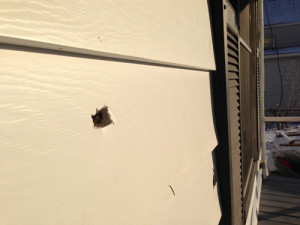 PAUL SQUIRE PHOTO | Three bullet holes could be seen in the front siding of the house.