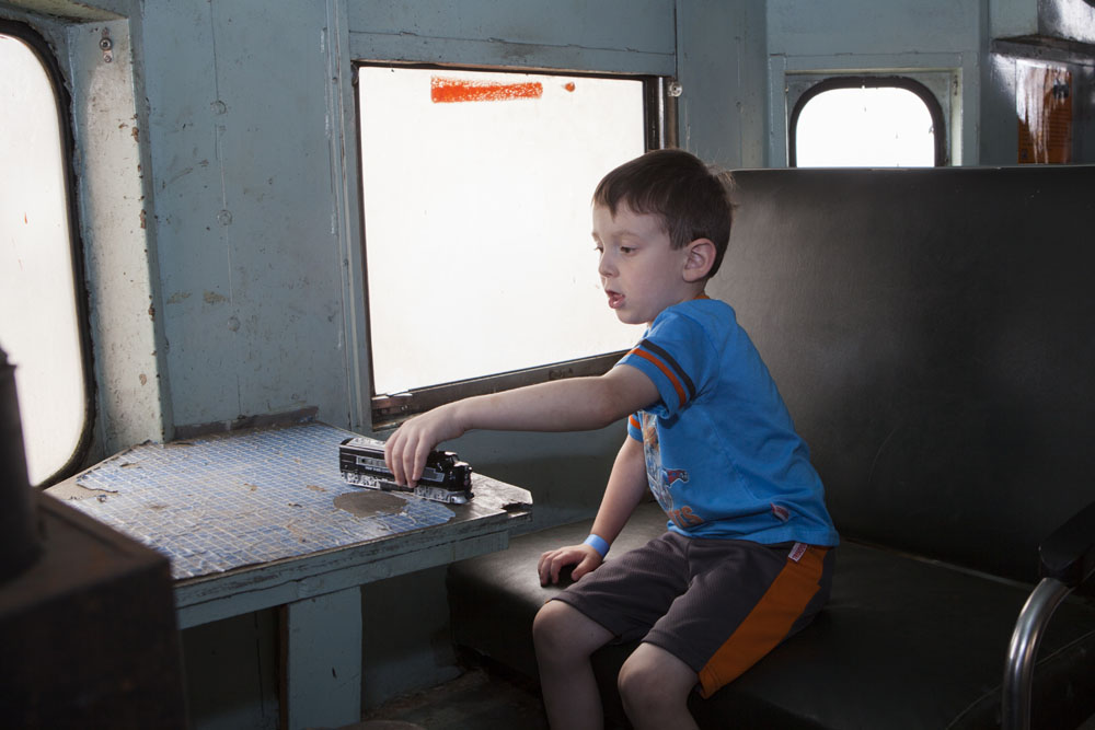 Pat Buffolino, 4, of Huntington plays with his toy train aboard a LIRR caboose. (Credit: Katharine Schroeder)