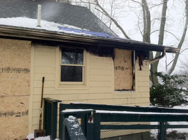 The damaged home was boarded up in spots Friday morning. (Credit: Michael White)