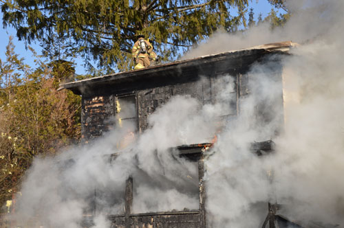 TOM LAMBUI PHOTO/LIHOTSHOTS.COM | Firefighters battle a Riverside Drive house fire from the roof Wednesday.