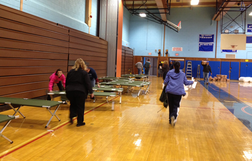 BETH YOUNG PHOTO | Setting up the storm shelter in Riverhead High School Sunday.