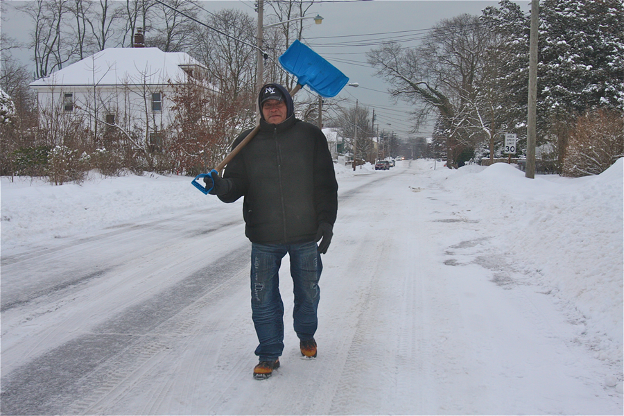 Santos Aguilar walks along Sweezy Avenue Monday morning in Riverhead to look for shoveling work. (Credit: Barbaraellen Koch)