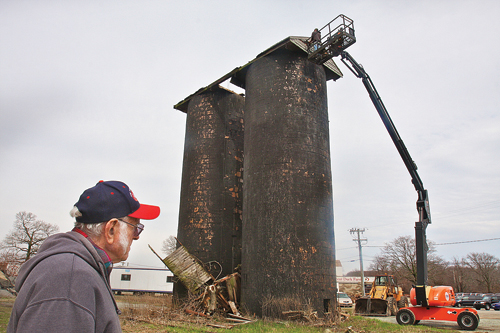 Lloyd Corwin, 80, watches as his grandson Blake gingerly tears down the old Purina feeds storage tower which was built from clay tiles and has deteriorated over the years since it was constructed after World War II next to the Crescent Duck Farm in Aquebogue. (Credit: Barbaraellen Koch, file)