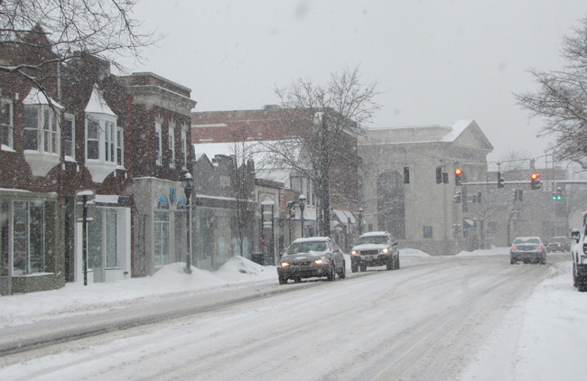 Cars make their way trough a snowy downtown Riverhead Thursday afternoon. (Credit: Tim Gannon)