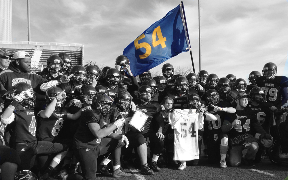 The No. 54 flag representing Tom Cutinella waves amid the Shoreham-Wading River players after Saturday's county championship win. (Credit: Joe Werkmeister)