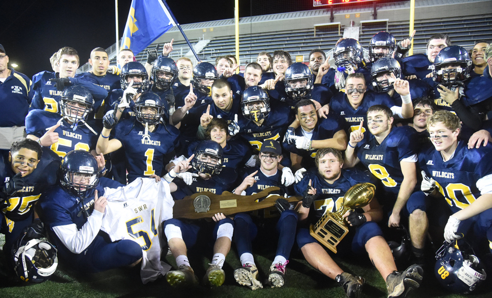 The Shoreham-Wading River football team celebrates its 2014 Long Island Championship win over Roosevelt. (Credit: Robert O'Rourk)