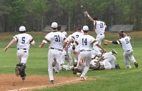 Shoreham-Wading River players are jubilant after Jack Massa scored on an infield error, capping a game-winning, four-run rally in the bottom of the seventh inning. (Credit: Robert O'Rourk)