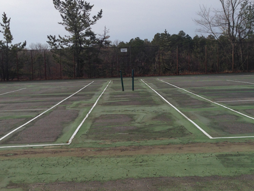 A view of two of Shoreham's tennis courts last spring, which have become unplayable after years of neglect. A proposed $48.5 million construction project would repair the courts. (Credit: Joe Werkmeister, file)