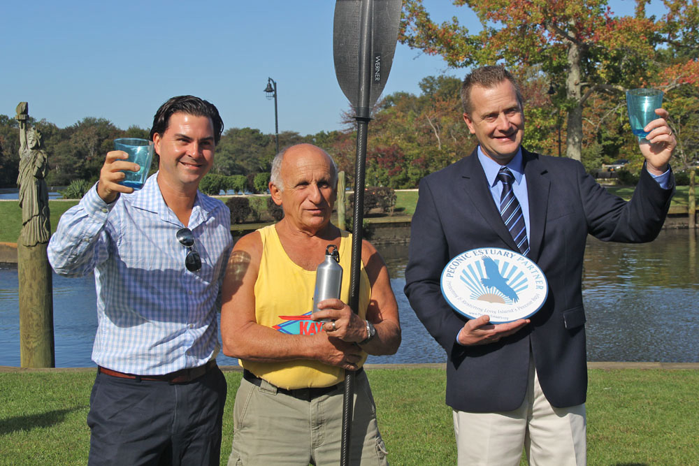 Aaron Virgin, VP of Group for the East End; Jim Dreeben, owner of Peconic Paddler; and Riverhead Supervisor Sean Walter down by the Peconic River on Friday morning. (Credit: Carrie Miller)