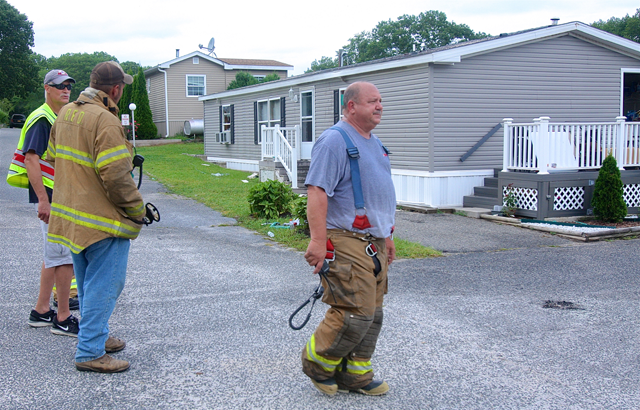 Riverhead Fire Department Chief Kevin Brooks (right) and other firemen at the scene.