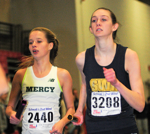 Meg Tuthill of McGann-Mercy races next to Kaitlyn Ohrtman of Shoreham-Wading River in the 4 x 800 relay. (Credit: Bill Landon)