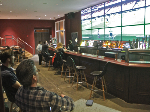 PAUL SQUIRE PHOTO | Joe Goglia (left) and another All-Star manager play a game of FIFA 13 on the bowling alley's 21-foot TV screen.