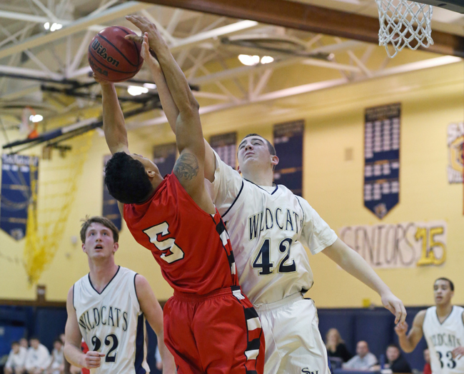 Shoreham-Wading River sophomore Ethan Wiederkehr goes up for a rebound against Mike Smith of Amityville. (Credit: Daniel De Mato)