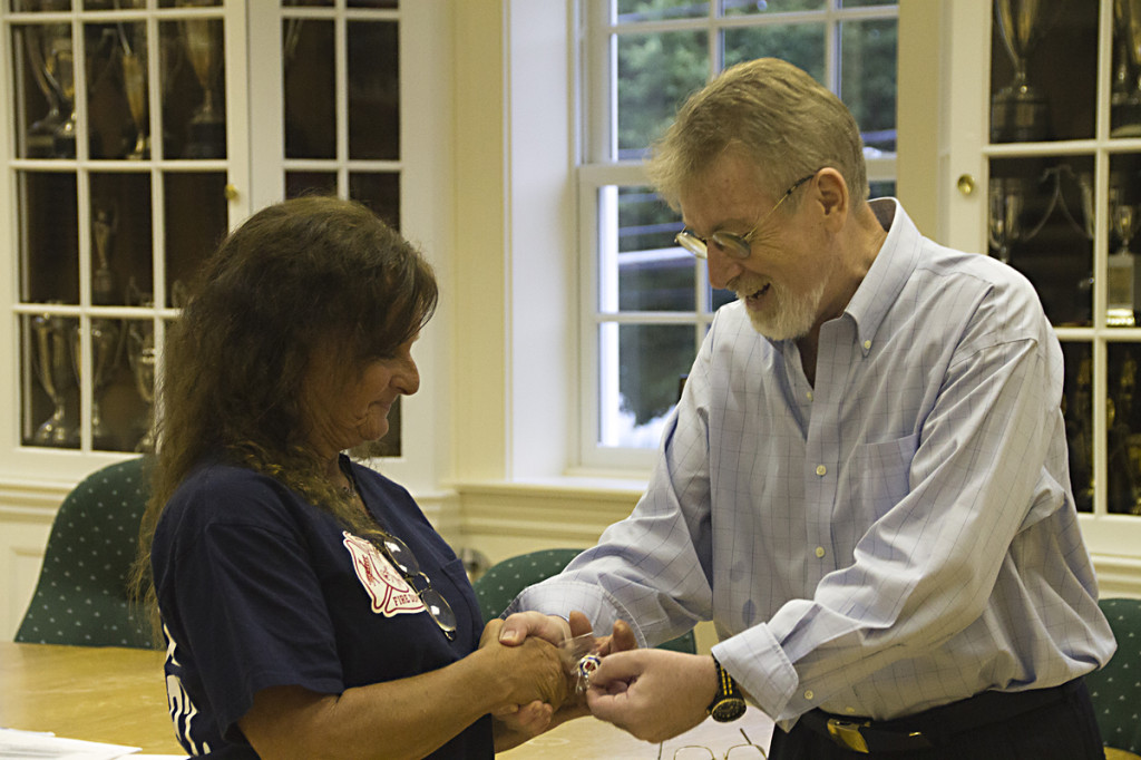 Heart attack survivor Joseph O'Byrne gives a special pin to Southold volunteer Renee Phelps, who performed CPR on Mr. O'Byrne and helped save his life in May. (Credit: Paul Squire)