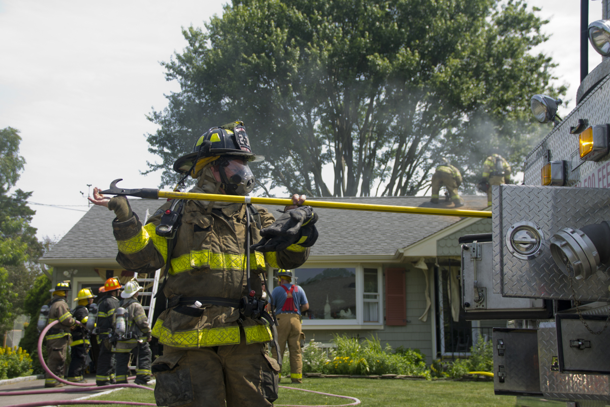 An East Marion firefighter grabs equipment from one of the fire trucks as volunteers knock down a house fire Thursday morning. (Credit: Paul Squire)