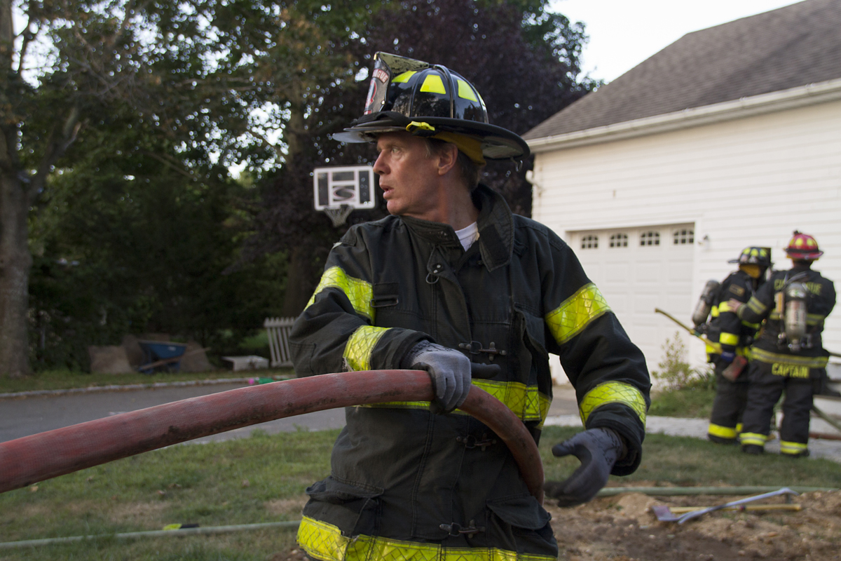 A Cutchogue firefighter helps lead a fire hose into the department's training scene Wednesday evening (Credit: Paul Squire)