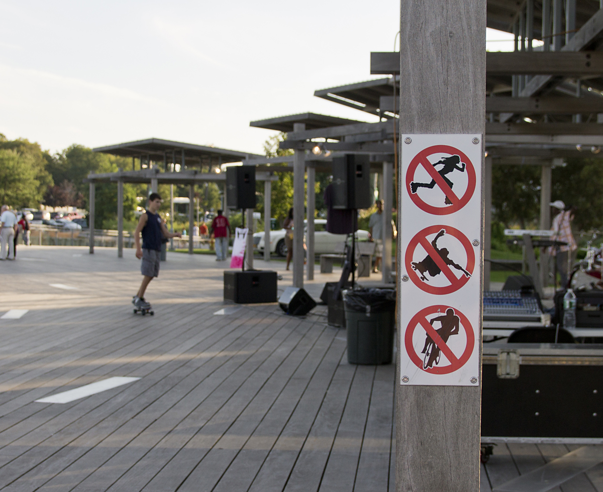 A teen skates near a no-skateboarding sign in Mitchel Park Monday evening. (Credit: Paul Squire)