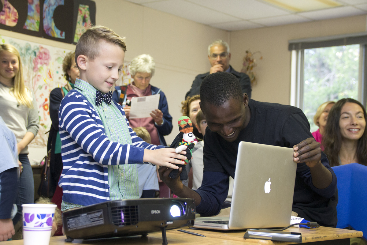 Peconic Community School lower primary student Sawyer Harbin shows the Zimbabwe schoolchildren the doll he bought during a live video conference Friday morning as Tinashe Basa, a nonprofit director, watches on. (Credit: Paul Squire)