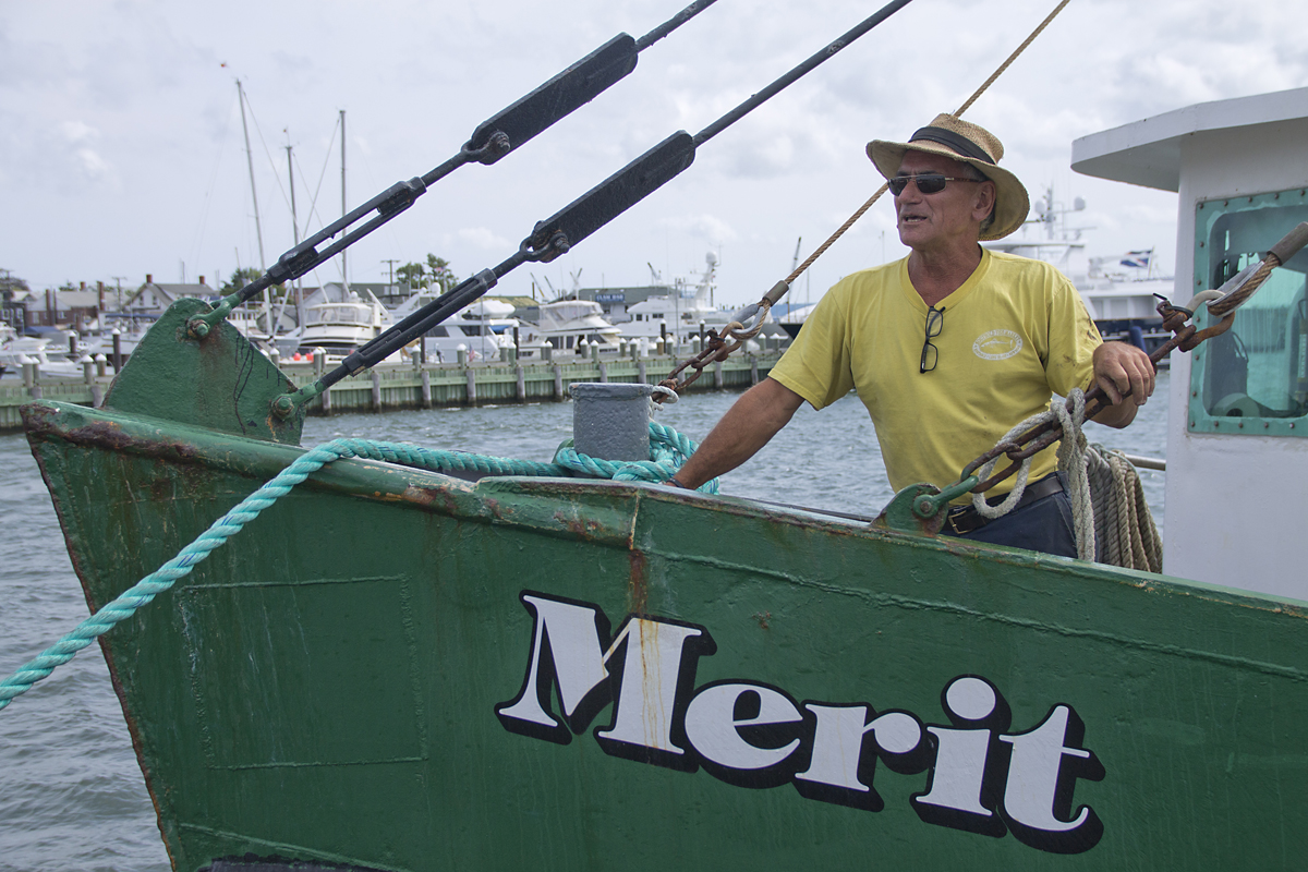Captain Sid Smith stands at the bow of the Merit in Greenport this summer. Mr. Smith and his two crew were dubbed heroes after they rescued four people who were thrown into stormy seas Wednesday night when their tugboat sank. (Credit: Paul Squire)