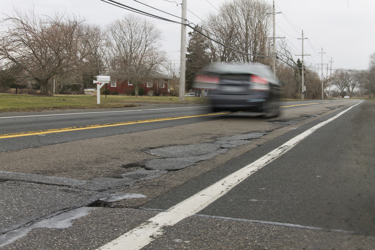 A driver speeds by a smattering of potholes on Route 48 in Southold Friday morning. (Credit: Paul Squire)