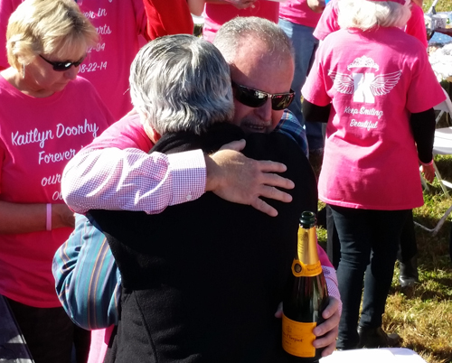 Kaitlyn's father, Joseph, wearing a pink memorial T-shirt, hugs Bill Araneo of Mattituck. (Credit: Greg Zuhoski photos)