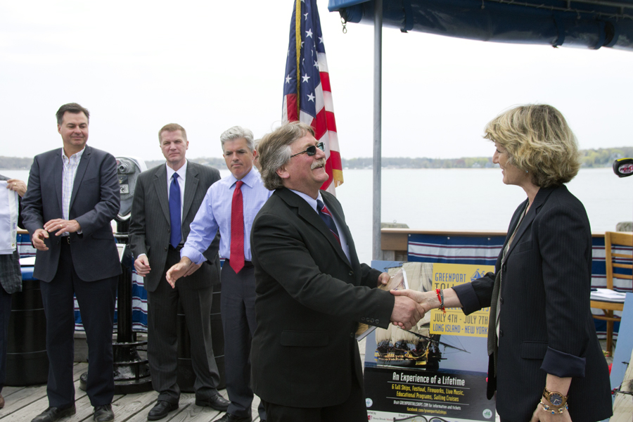 Greenport Mayor George Hubbard shakes hands with Judi Kilachand, executive director of the Friends of Hermione-LaFayette in America. (Credit: Paul Squire)