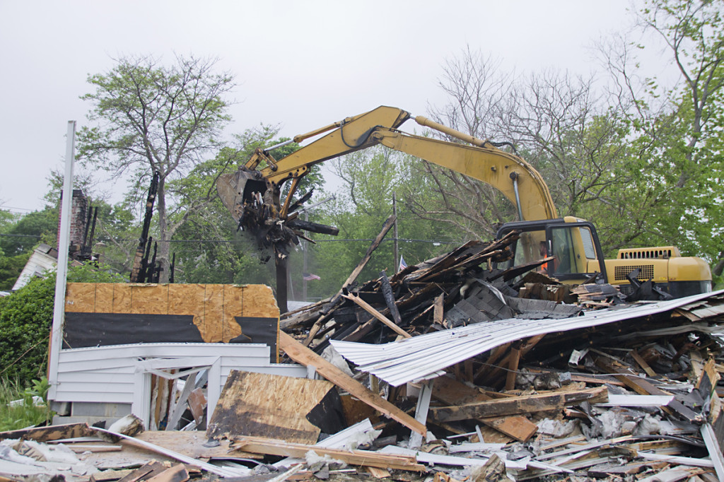 Construction crews load the remains of the First Universalist Church into dumpsters at the site Thursday morning.
