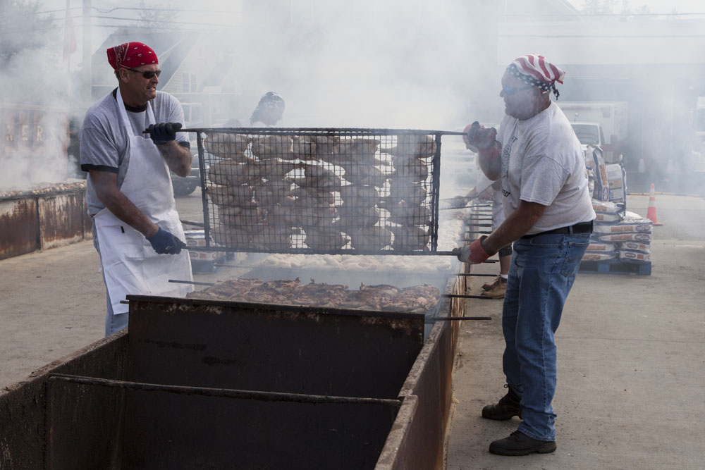 Mike Finnigan, left, and Teddy Behr flip the chicken. (Credit: Katharine Schroeder)