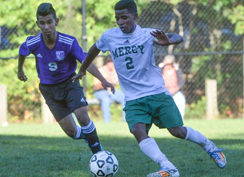 Bishop McGann-Mercy's Bereket Watts turns the ball upfield against Hampton Bays' Loaiza Cristian. (Credit: Robert O'Rourk)