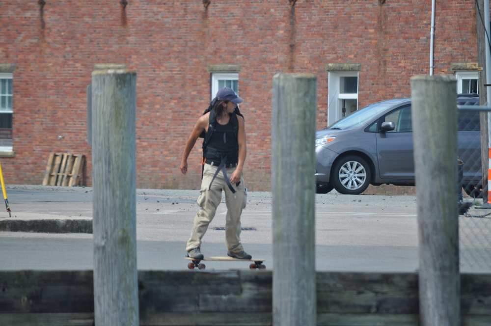 A skateboarder down by the ferry dock.