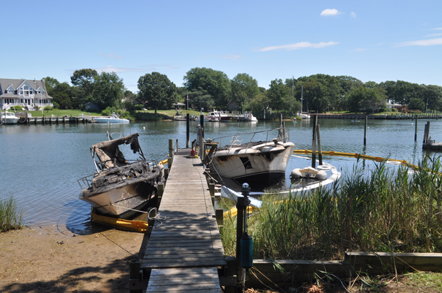 A smaller boat (left) was destroyed after the engine to a yacht (right) caught fire Saturday night on the edge of Gull Pond in Greenport. (Credit: Grant Parpan)