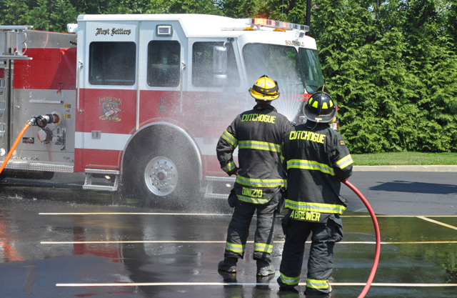 Cutchogue Fire Department members hose down Southold's new pumper. (Credit: Grant Parpan)