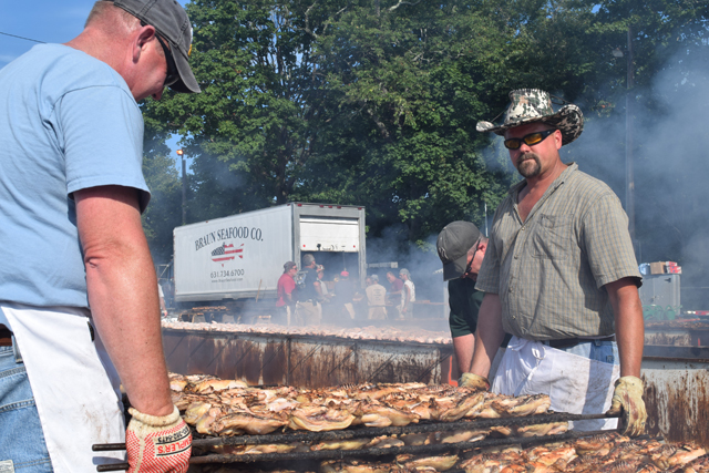 Cutchogue Fire Depatrment members Ben Benediktsson and Will Park (right) tend to the enormous grill. (Credit: Vera Chinese)