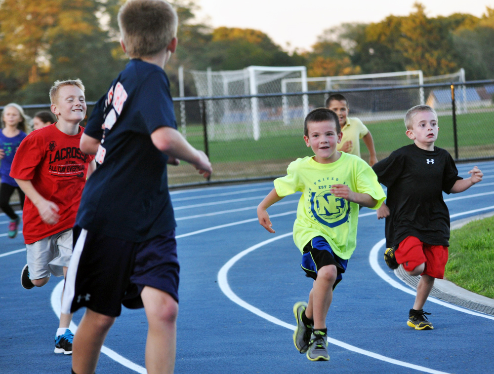 Members of the community, including these youngsters, took the first lap around the new Mattituck High School track together Friday evening. (Credit: Grant Parpan)