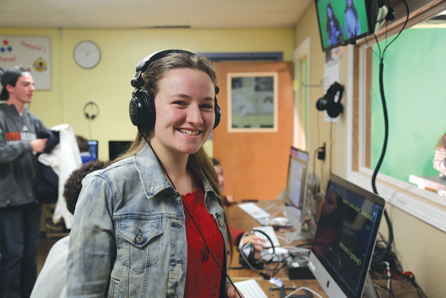 Southold senior Daisy Rymer during class last Thursday. As co-producer, she talks to the anchors through a headset, sets up equipment for filming and edits the news show. (Credit: Krysten Massa)