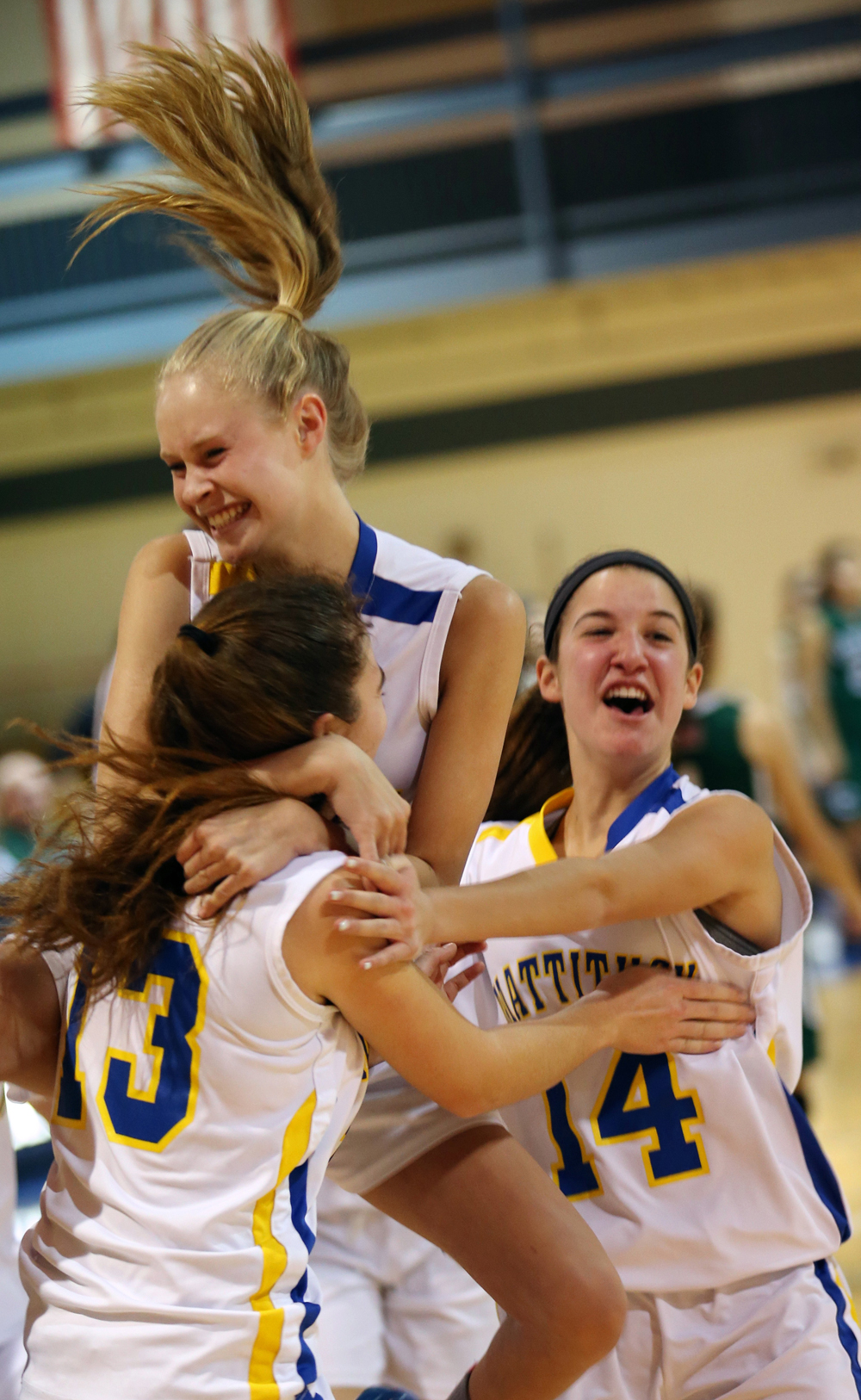 Emily Mowdy jumps into the arms of Liz Dwyer, left, as  Jane DiGregorio joins in the celebrating after Mattituck. (Credit: Garret Meade)