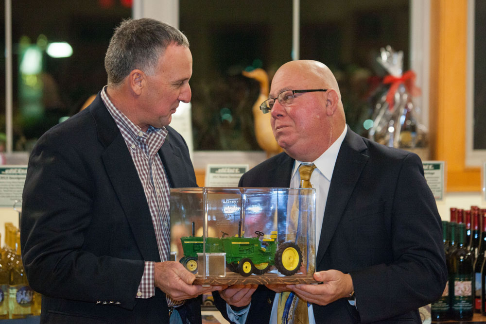 Former Farm Bureau president Mark Zaweski presents Joe Gergela with a miniature tractor as a memento. Also in the presentation case is a small container of soil from Joe's Jamesport farm. (Credit: Katharine Schrieder)