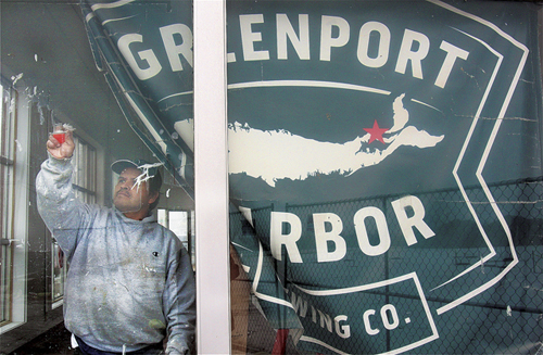 Greenport Harbor Brewing Company worker Enfivfo Cruz cleans windows that line the former Lucas Ford showroom on Main Road in Peconic. (Credit: Barbaraellen Koch, file)