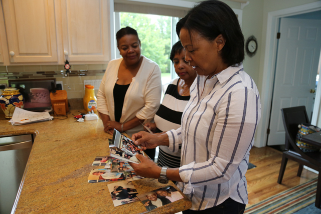 Katherine Hubbard combs through family photos along with sisters Janice Barnez and Marie Hubbard-Brown. (Credit: Krysten Massa)