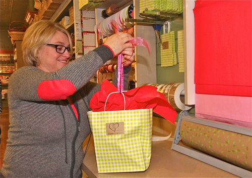 Jackie Wilsberg, Love Lane Sweet Shop owner, ties up a gift on Thursday. Barbaraellen Koch photo.